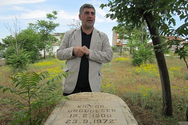 Serdar Boyaci showing his grandfather's gravestone