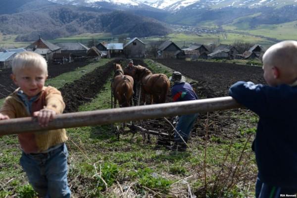 Children watch as a farmer plows his field.