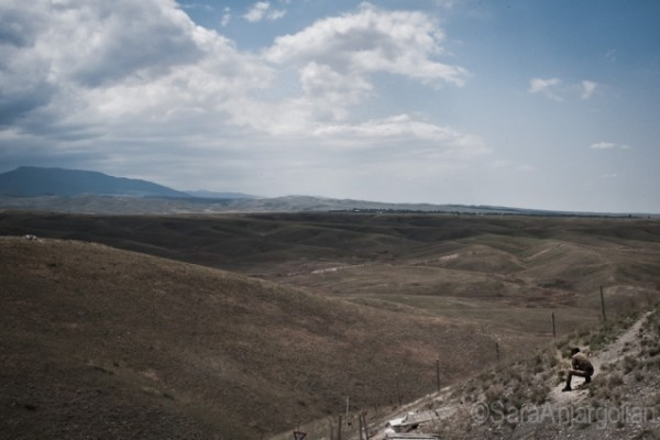 A soldier makes a call at the only spot with cell phone reception at the Mataghis frontline. The Azerbaijani frontline is visible in the foreground with an Azerbaijani village in the background. Nagorno-Karabakh.