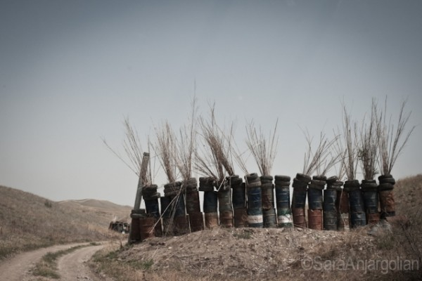 On the road to the Mataghis frontline, an exposed portion of the road, visible from the Azerbaijani frontline, is partially fortified against gunfire by large metal canisters, tires, and hay.