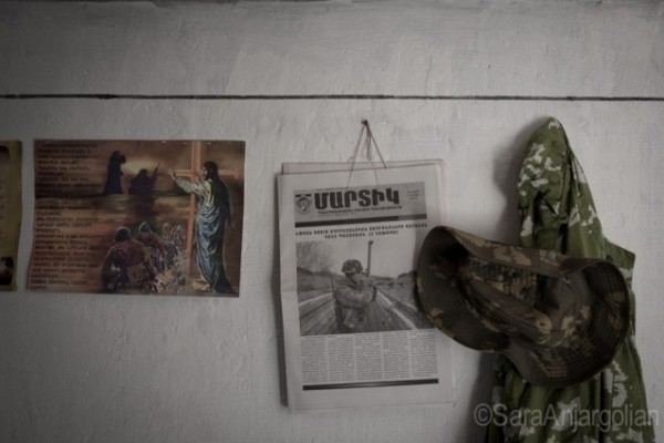 On the walls of a dugout on the Mataghis frontline hang a religious poster discouraging violence among the military ranks, a copy of the Nagorno-Karabakh Republic's official military newspaper, and a soldier's hat and jacket.