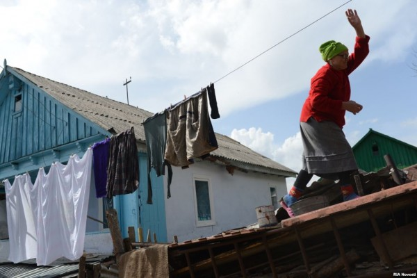 A villager hangs clean linens.